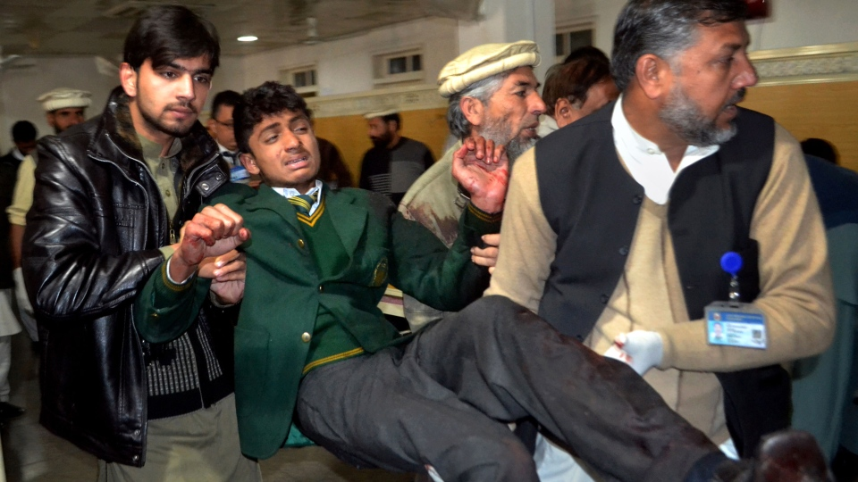 Pakistani volunteers carry a student injured in the shootout at a school under attack by Taliban gunmen, at a local hospital in Peshawar, Pakistan, Tuesday, Dec. 16, 2014. (AP / Mohammad Sajjad)