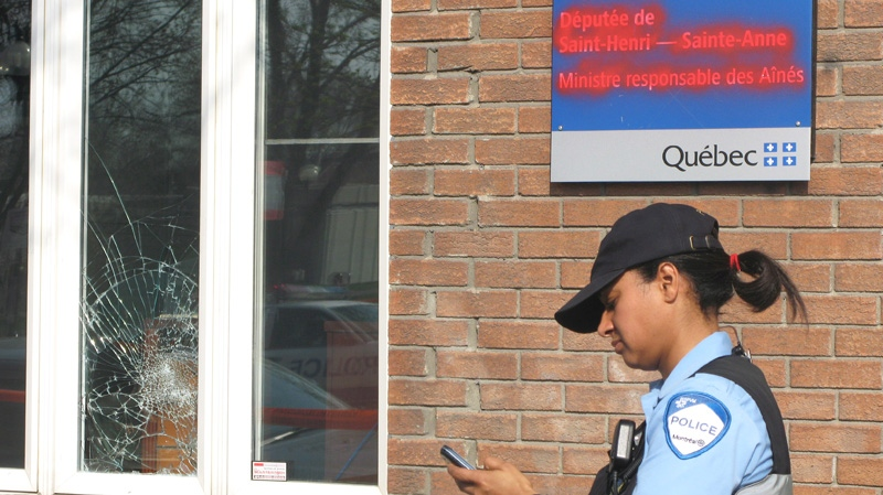 A police officer looks at her phone outside the damaged office of Marguerite Blais, the Quebec minister responsible for seniors, in Montreal, Monday, April 16, 2012. (Peter Ray / THE CANADIAN PRESS)