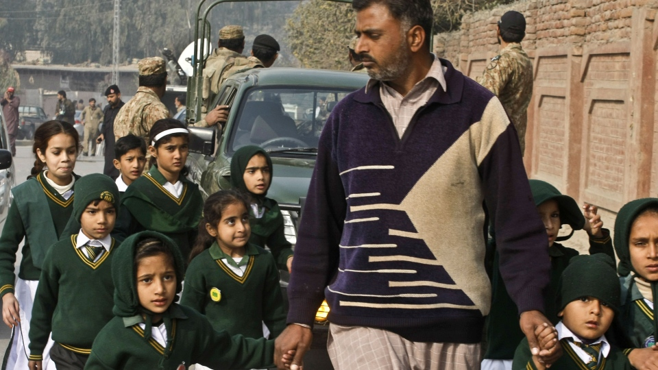 A plainclothes security officer escorts students rescued from nearby school during a Taliban attack in Peshawar, Pakistan, Tuesday, Dec. 16, 2014. (AP / Mohammad Sajjad)