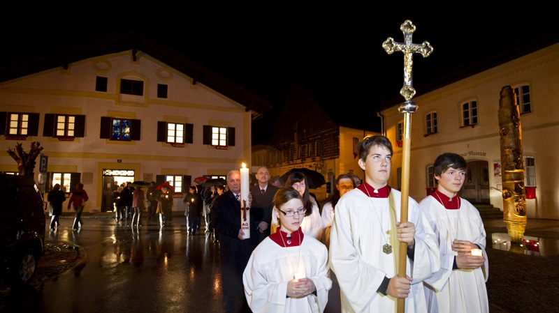 Believers walk from the house where pope Benedict XVI was born to the church for prayers in Marktl, southern Germany, early Monday, April 16, 2012, to celebrate the pope's 85th birthday. (AP Photo/dapd, Lukas Barth)