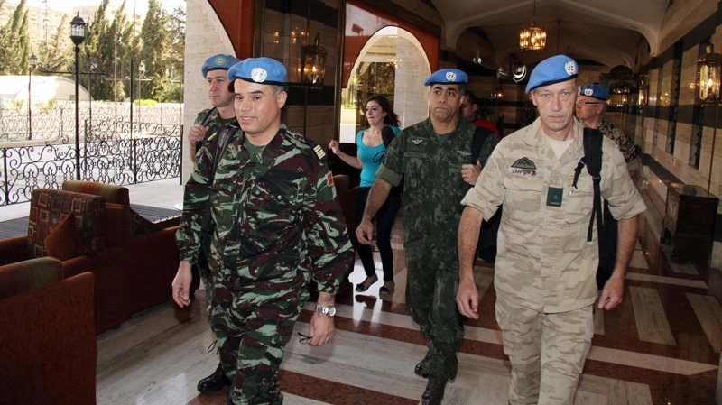 UN observers, led by Moroccan Col. Ahmed Himmiche, left, leave the Sheraton Hotel in Damascus, Syria, Monday, April 16, 2012. (AP Photo/Bassem Tellawi)