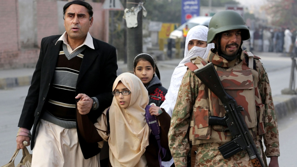 Pakistani parents escort their children outside a school attacked by the Taliban in Peshawar, Pakistan, Tuesday, Dec. 16, 2014. (AP / B.K. Bangash)
