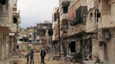 Syrians walk between destroyed buildings in the Inshaat neighborhood of Homs, Syria, Sunday, April 15, 2012. (AP Photo)