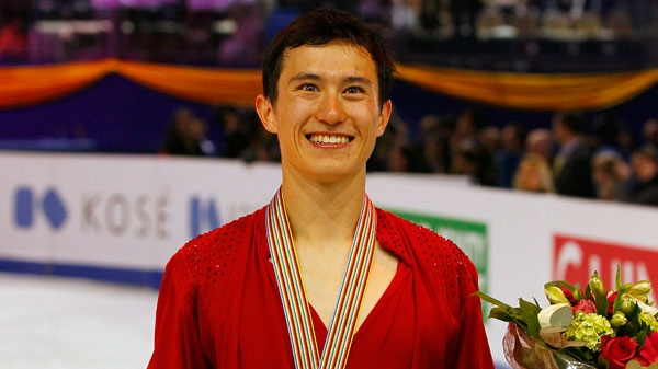 Patrick Chan holds the Canada flag after the Men Free skating in France, Saturday, March 31, 2012. (AP / Francois Mori)