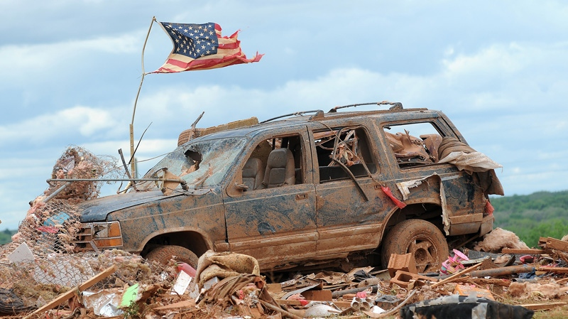 A tattered American flag flies over a vehicle where two young girls ages 5 and 7 were found after a severe thunderstorm spawned a massive tornado at Hideaway Mobile Home Villa in Woodward, Oklahoma shortly after midnight Sunday, April 15, 2012. (AP Photo/ENID NEWS and EAGLE, BONNIE VCULEK)