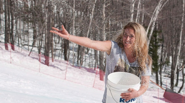 A course volunteer throws a salt mixture to harden the snow as warm weather sets on the hill during the men's downhill Canadian Championship race Tuesday, March 20, 2012. (Jacques Boissinot / THE CANADIAN PRESS)