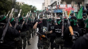 Palestinian Hamas masked gunmen march in a rally to commemorate the 27th anniversary of the Hamas militant group, in Gaza City, Sunday, Dec. 14, 2014. (AP Photo/Khalil Hamra)