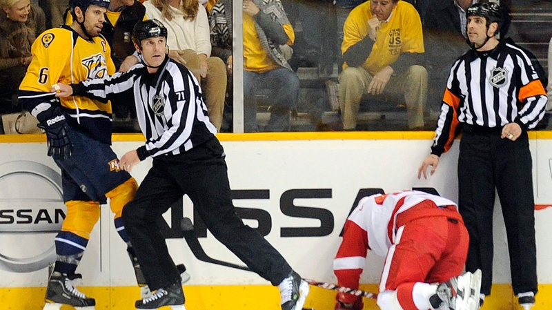 Nashville Predators defenseman Shea Weber is moved away from Detroit Red Wings centre Henrik Zetterberg by linesman Brad Kovachik after he slammed Zetterberg's head against the glass at the end of Game 1 of a first-round NHL hockey playoff series in Nashville, Tenn, on Wednesday, April 11, 2012. (The Tennessean, Sanford Myers)