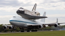 The space shuttle Discovery, sitting atop a 747 carrier aircraft, lands at Dulles International Airport in Chantilly, Va., Tuesday, April 17, 2012. (AP / Manuel Balce Ceneta)