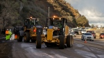 Caltrans crews work to clean up a torrent of mud and rocks covering part of State Route 91 in Orange County early Wednesday, Dec. 17, 2014, in Yorba Linda, Calif. Cars and trucks were stuck for several hours, but no injuries were reported. (AP/Chris Carlson)
