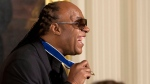 Musician Stevie Wonder smiles and shows his Presidential Medal of Freedom after being awarded the medal by President Barack Obama, Monday, Nov. 24, 2014, during a ceremony in the East Room of the White House in Washington. (AP/Jacquelyn Martin)