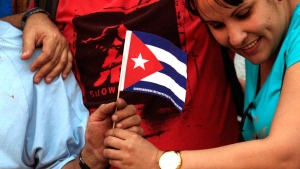 Cuban citizens living in Chile, hold a Cuban flag while celebrating the restoration of diplomatic relations between the island nation and the United States, in the courtyard of the Cuban Embassy in Santiago, Chile, Wednesday Dec. 17, 2014. (AP / Luis Hidalgo)