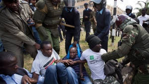 Protesters are beaten with wooden clubs and arrested by riot police outside the Parliament building in Nairobi, Kenya, on Dec. 18, 2014. (AP / Ben Curtis)