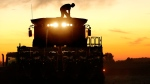 In this Sept. 27, 2014 file photo, a corn farmer on top of his combine is silhouetted against the setting sun while harvesting corn in Pleasant Plains, Ill. U.S. agriculture has a big appetite for freer trade with Cuba, and corn is one of the main products Cuba now buys from the United States. (AP/Seth Perlman, File)