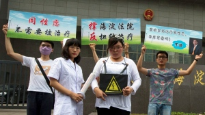 Gay rights campaigners pose for journalists to protest outside a court where the first court case in China involving so-called conversion therapy is held in this file photo taken in Beijing, China, on Thursday, July 31, 2014. (AP / Ng Han Guan)