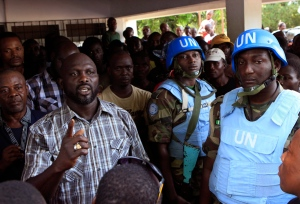 Opposition leader George Weah, left, is protected by United Nations peacekeepers from Nigeria as he speaks to supporters in Monrovia, Liberia on Nov. 9, 2011. The former soccer star is running for a Senate seat. (Rebecca Blackwell / AP Photo)