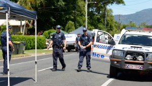 Police patrol near a house where eight children have been found dead in a Cairns suburb in far north Queensland, Australia, Friday Dec 19, 2014. (AP Photo/Graeme Bint)