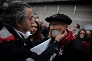 A demonstrator covers the mouth of 84-year-old Periko Salaberria, right, during a protest against Spanish Citizens Security Law, in Bilbao, northern Spain, Dec. 20, 2014. Spaniards protested on Saturday against the Citizen Security Law that was approved by the Government last December 11. (Alvaro Barrientos / AP Photo)