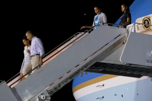 President Barack Obama walks with Sasha Obama as first lady Michelle Obama walks with Malia Obama, as the first family arrives at Pearl Harbor, Hawaii to begin their family vacation Friday, Dec. 19, 2014. (AP/Jacquelyn Martin)