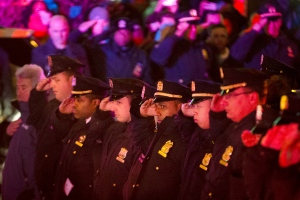 Mourners stand at attention as the bodies of two fallen NYPD police officers are transported from Woodhull Medical Center, Saturday, Dec. 20, 2014, in New York. An armed man walked up to two New York Police Department officers sitting inside a patrol car and opened fire Saturday afternoon, killing one and critically wounding a second before running into a nearby subway station and committing suicide, police said. (AP /John Minchillo)