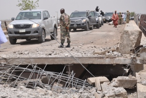 In this Sunday, May 11, 2014 file photo, A soldier and government officials inspects the bridge that link Nigeria and Cameroon following an attacked by Islamic militants in Gambaru, Nigeria. (Jossy Ola / AP Photo)
