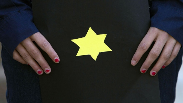 A girl holds a booklet with a yellow Star of David, symbolizing the sign identifying Jews during World War II, as Israeli activists hold a ceremony outside the German embassy in Tel Aviv, Israel on Holocaust Remembrance Day, Thursday, April 19, 2012. (AP Photo/Dan Balilty)