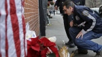 Police officers leave candles at an impromptu memorial near the site where two New York City police officers were killed in the Brooklyn borough of New York, Sunday, Dec. 21, 2014. (AP / Seth Wenig)