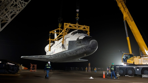 space shuttle Discovery is suspended from a sling held by two cranes after the Boeing 747 carrier backed away at Washington Dulles International Airport, Thursday, April 19, 2012, in Sterling, Va.(NASA / Bill Ingalls)