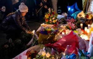 A mourner places a candle Sunday, Dec. 21, 2014, at a memorial near the spot where two New York Police Department officers, sitting inside a patrol car the previous day, were shot by an armed man, killing them both. (AP / Craig Ruttle)