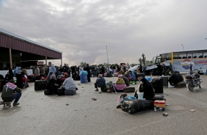 Palestinians wait near their luggage to cross the border to the Egyptian side at Rafah crossing in the southern Gaza Strip, Sunday, Dec. 21, 2014. (AP Photo/Adel Hana)