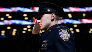 New York Police Department officer Jason Muller salutes during the national anthem after participating in a moment of silence for two slain NYPD officers before an NBA basketball game between the Brooklyn Nets and the Detroit Pistons in New York on Sunday, Dec. 21, 2014. (AP / Jason DeCrow)