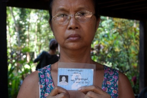 In this photo taken on Nov. 16, 2014, Aye Pu, mother of May Aye Nwe, 20, who was lost at sea during the Indian Ocean tsunami in 2004, holds up her daughter's student identification card during an interview at her home in Seint Paing, Myanmar. (AP Photo/Khin Maung Win)