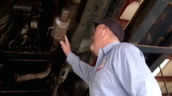A mechanic gestures towards a catalytic converter under a vehicle in this undated image taken from video.
