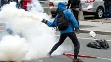 A demonstrator throws tear gas canister back towards the police line during a student demonstration outside the Montreal Convention Centre against hikes to university and college tuition fees Friday, April 20, 2012 in Montreal. (Paul Chiasson / THE CANADIAN PRESS)