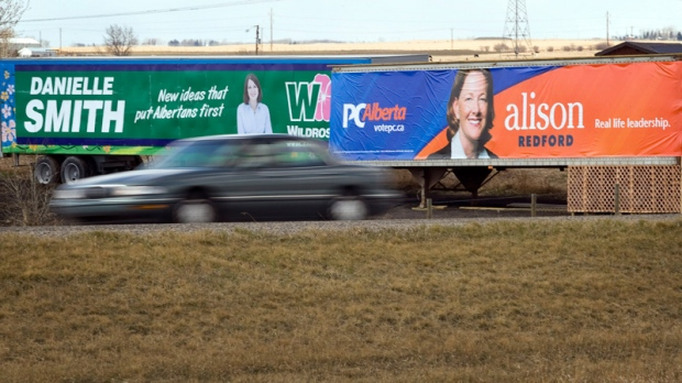 Billboards picturing Alberta PC Leader Alison Redford, right, and Wildrose Leader Danielle Smith look out over traffic on Queen Elizabeth Highway II near Highriver, Alta., Thursday, April 19, 2012. (Jeff McIntosh / THE CANADIAN PRESS)
