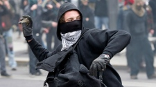 A demonstrator throws a rock towards the police line during a student demonstration outside the Montreal Convention Centre against hikes to university and college tuition fees Friday, April 20, 2012 in Montreal. (Paul Chiasson / THE CANADIAN PRESS)