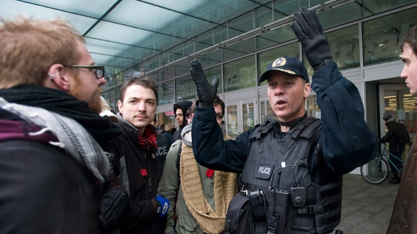 A police officer speaks with protesters outside a conference centre in Montreal Saturday, April 21, 2012. (Graham Hughes / THE CANADIAN PRESS)