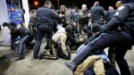 Police try to control a crowd on the lot of a gas station following a shooting in Berkeley, Mo., Wednesday, Dec. 24, 2014. (St. Louis Post-Dispatch / David Carson)