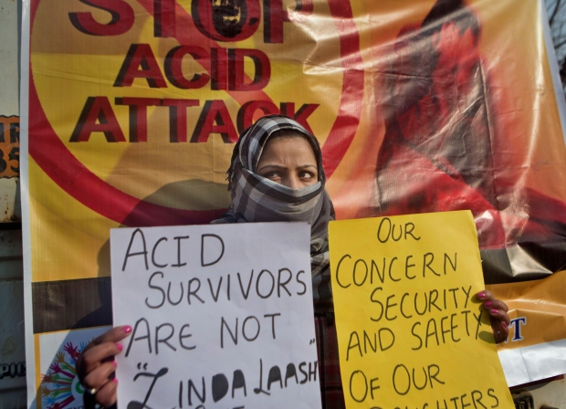 In this Dec. 12, 2014 file photo, Kashmiri law student Fareen holds placards as she participates in a protest against an acid attack on a woman. (AP Photo/Dar Yasin)