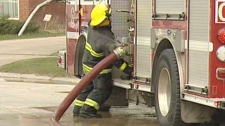 A firefighter works to secure a hose at the scene of a fire in the northwestern part of Winnipeg Saturday afternoon.