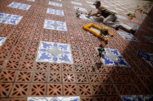 A man climbs to place roses onto a tiled memorial wall displaying names of victims from the Asian tsunami, in Phang Nga, Ban Nam Khem province, Thailand, Friday, Dec. 26, 2014. December 26 marks the 10th anniversary of one of the deadliest natural disasters in world history. (AP Photo/Wong Maye-E)