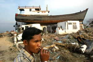 In this Feb. 17, 2005 file photo, an Acehnese man smokes a cigarette near a house on which a fishing boat landed after it was swept away by tsunami in Banda Aceh, Aceh province, Indonesia. Friday marks the 10th anniversary of one of the deadliest natural disasters in world history: a tsunami, triggered by a massive earthquake off the Indonesian coast, leaving more than 230,000 people dead in 14 countries and causing about $10 billion in damage. (AP Photo/Dita Alangkara, File)