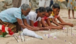 Sri Lankan tsunami survivors pay their respect at a mass grave of 591 train passengers which was hit by 2004 tsunami in Peraliya, Sri Lanka, Friday, Dec. 26, 2014. In Sri Lanka the train 591, which was tossed up by the waves and the charred images of which became an icon of the disaster, carried some survivors, relatives of the dead and the guard who was on duty 10 years ago, stopped at the disaster site for a remembrance of the dead.  (AP Photo/Eranga Jayawardena)