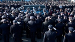 Police officers salute as the hearse of New York City police officer Rafael Ramos drives along his funeral procession route in the Glendale section of Queens, Saturday, Dec. 27, 2014. (AP / John Minchillo)