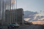This Dec. 17, 2014 file photo shows a classic American car driving past the U.S. Interests Section building in Havana, Cuba. A half-century after Washington severed relations with Cuba, the seven-story mission is set to become a full-fledged embassy.  (AP/Desmond Boylan, File)