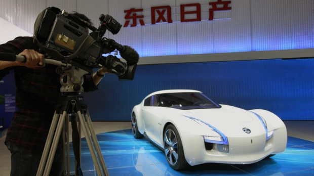 A cameraman films Nissan's latest concept and electronic car the Esflow at the Beijing International Auto Exhibition in Beijing, China, Monday, April 23, 2012. (AP Photo/ Vincent Thian)
