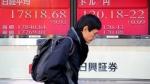 A man walks by an electronic stock board of a securities firm in Tokyo, Friday, Dec. 26, 2014. (AP/Koji Sasahara)