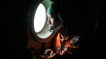 A crew of an Indonesian Air Force C-130, of the 31st Air Squadron, looks out of the window during a search operation for the missing AirAsia Flight 8501 jetliner over the waters of Karimata Strait in Indonesia, Monday, Dec. 29, 2014. (AP / Dita Alangkara)