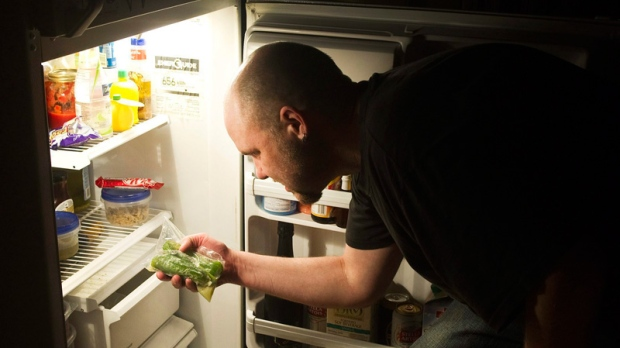 Bryan Kautz looks in his fridge in Toronto on Thursday, May 12, 2011. (Nathan Denette  / THE CANADIAN PRESS)