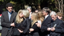 Friends and family of Nik Zoricic embrace each other following his funeral in Toronto on Monday, March 19, 2012. (Pawel Dwulit / THE CANADIAN PRESS)